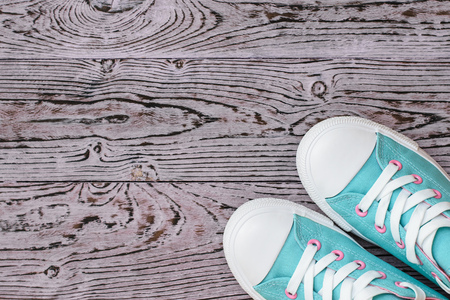 Turquoise and pink sneakers on the wooden floor. Sports style. Flat lay. The view from the top.