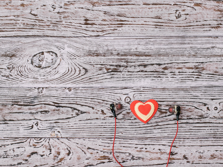 Headphones and red and white heart on wooden background. Romantic style in fashionable clothes. Flat lay. The view from the top.