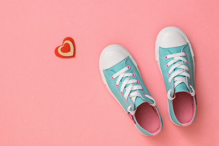 Turquoise sneakers and a red and white heart on a pink background. Color trend 2019. Sports style. Flat lay. The view from the top.