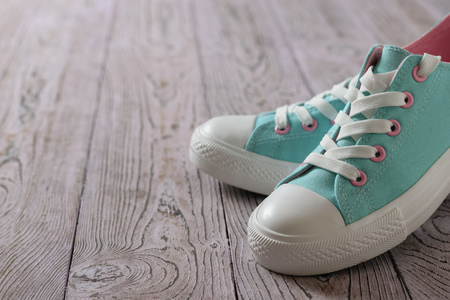 Beautiful turquoise sneakers on the wooden floor. Sport style.