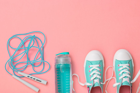 Turquoise sneakers and a high-speed jump rope on a pink background. Sports style. Flat lay. The view from the top.
