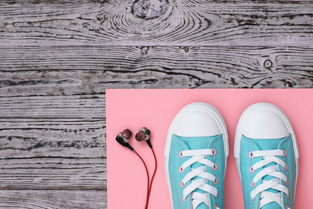 Sneakers on a coral rug and headphones on a wooden floor. Sports style. Flat lay. The view from the top. Stock Photo - 125292382