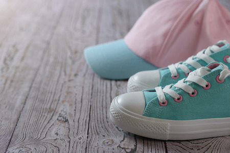 Turquoise sneakers and a pink and turquoise cap on the wooden floor. Sport style.