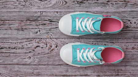 A pair of turquoise sneakers on a textured wooden floor. Sports style. Flat lay. The view from the top. Reklamní fotografie