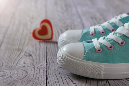 Turquoise sneakers and a red and white heart on the wooden floor. Sport style.
