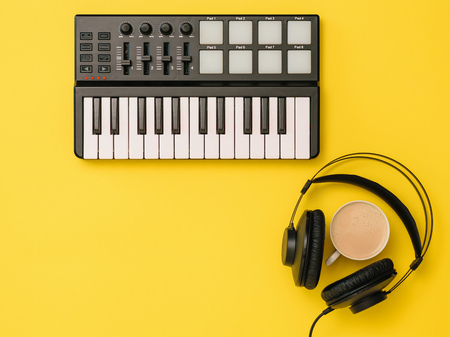 Headphones, coffee and music mixer on yellow background. The concept of workplace organization. Equipment for recording, communication and listening to music. Reklamní fotografie