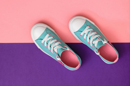 Turquoise sneakers on a background of pink and purple paper. Color trend 2019. Sports style. Flat lay. The view from the top.