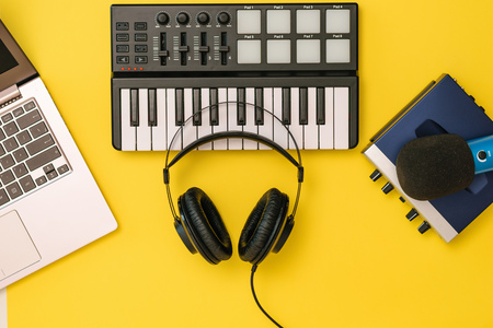Headphones on music mixer, laptop and sound card on yellow background. The concept of workplace organization. Equipment for recording, communication and listening to music. Reklamní fotografie