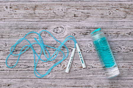 Blue jump rope and blue water bottle on wooden background. Sports style. Flat lay. The view from the top.