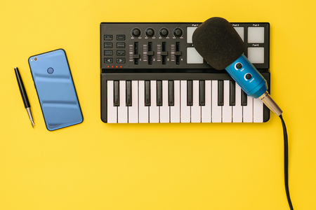 Microphone, mixer, smartphone and pen on yellow background. The concept of workplace organization. Equipment for recording, communication and listening to music.