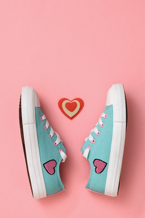 A pair of beautiful sneakers and a red and white heart on a pink background. Color trend 2019. Sports style. Flat lay. The view from the top.
