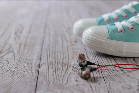 Black headphones with red wire on the floor next to turquoise sneakers. Sport style. Stock Photo - 125292506