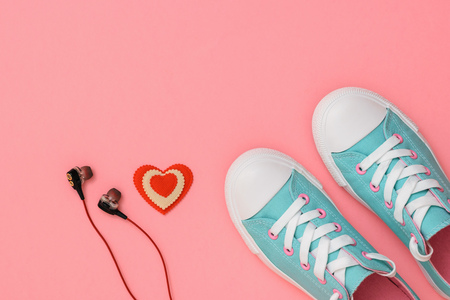 Headphones, red and white heart and turquoise sneakers on pink background. Color trend 2019. Sports style. Flat lay. The view from the top.