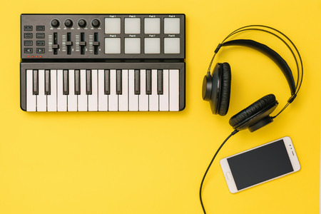 Smartphone, music mixer and headphones on bright yellow background. The concept of workplace organization. Equipment for recording, communication and listening to music.
