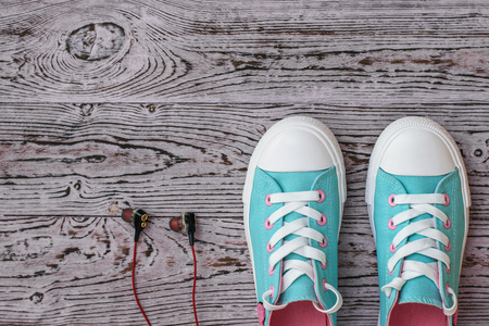 Black headphones with red wire and turquoise sneakers on the wooden floor. Sports style. Flat lay. The view from the top.