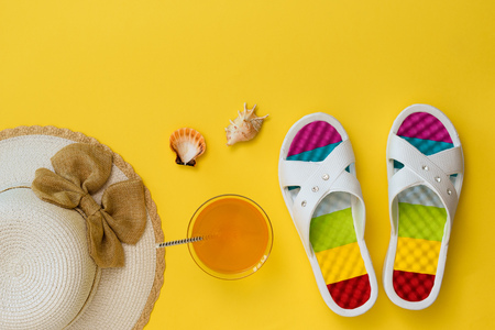 Colorful shoes, hat and orange drink on yellow background. The concept of summer vacation. Flat lay. The view from the top.