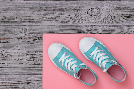 Turquoise sneakers on a red rug on a wooden floor. Sports style. Flat lay. The view from the top.