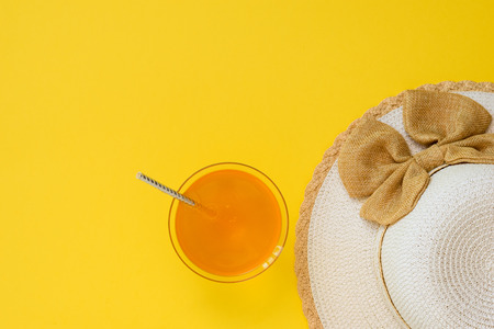 Hat and orange drink in bowl with cocktail straw on yellow background. The concept of summer vacation. Flat lay. The view from the top. 스톡 콘텐츠