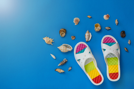 Colorful womens shoes and seashells on a blue background. The concept of a holiday by the sea. Flat lay. The view from the top.
