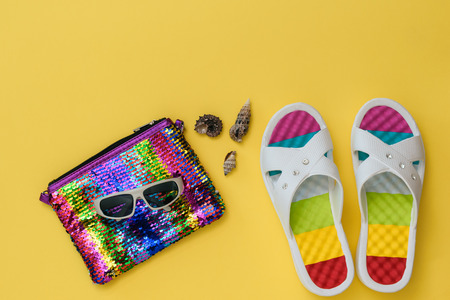 Colorful shoes for women, seashells, sunglasses and a bag on a bright yellow background. The concept of summer vacation. Flat lay. The view from the top.