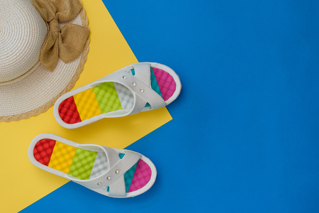 Hat and colorful shoes for women on blue and yellow background. The concept of a holiday by the sea. Flat lay. The view from the top.