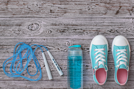 Turquoise sneakers and a high-speed jump rope on a wooden floor. Sports style. Flat lay. The view from the top. Stock Photo - 125292567