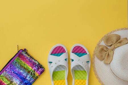Hat, multi-colored shoes and bag on a yellow background. The concept of summer vacation. Flat lay. The view from the top. 스톡 콘텐츠
