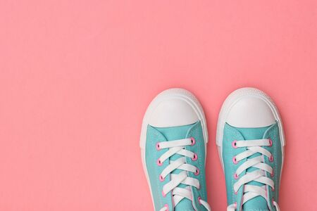 A pair of turquoise sneakers on a pink background. Color trend 2019. Sports style. Flat lay. The view from the top.