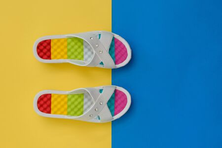 Summer colorful shoes for women on yellow and blue background. The concept of a holiday by the sea. Flat lay. The view from the top. 스톡 콘텐츠