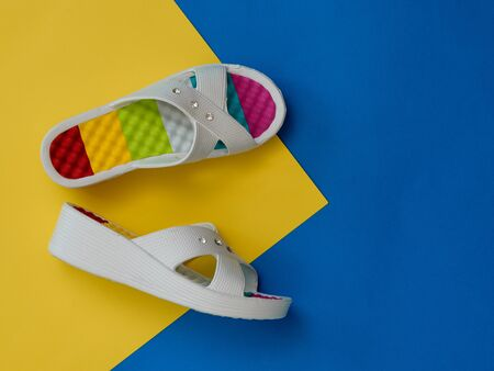 Colorful woman shoes on blue and yellow background. The concept of a holiday by the sea. Flat lay. The view from the top.