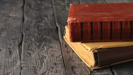 Two very old books on a black wooden table. Literature of the past. Stock Photo