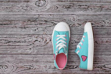Turquoise sneakers with embroidered heart on the wooden floor. Sports style. Flat lay. The view from the top. Reklamní fotografie