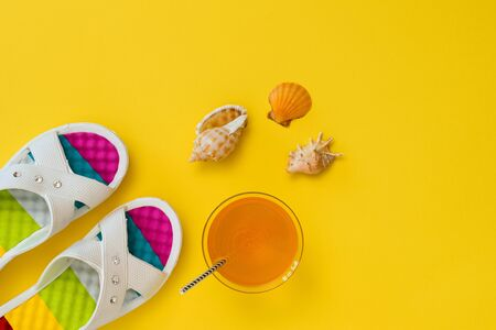 Orange drink with colorful shoes and shells on yellow background. The concept of summer vacation. Flat lay. The view from the top.