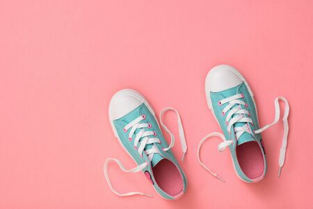 A pair of turquoise sneakers with laces on a pink background. Color trend 2019. Sports style. Flat lay. The view from the top.