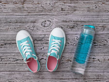 Turquoise sneakers with pink soles and a water bottle on the wooden floor. Sports style. Flat lay. The view from the top. Reklamní fotografie