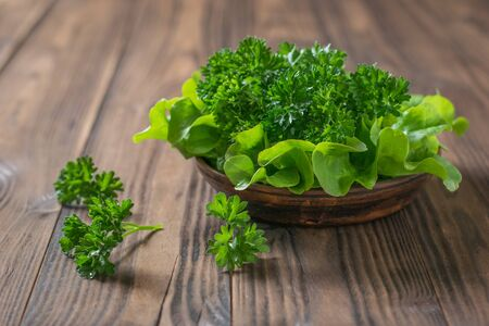 Lettuce and parsley in a clay bowl on a wooden table with a fork. The concept of healthy eating. Banco de Imagens