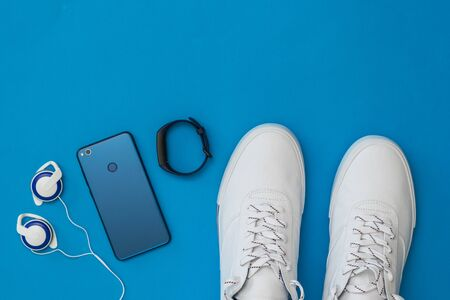 White sneakers, headphones, smart bracelet and blue smartphone on blue background. Sports style. Flat lay. The view from the top.