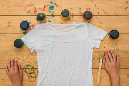 The child is preparing to apply paint on a t-shirt in the style of tie dye. Staining fabric in tie dye style. Stock Photo