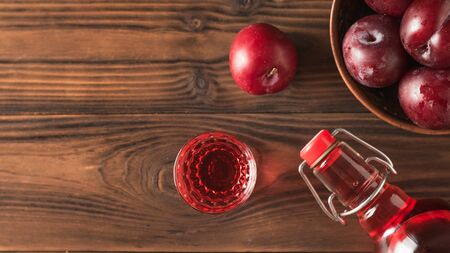 Plum alcoholic drink and plum berries on the brown table. Homemade alcoholic drink made from berries plum. Flat lay The view from the top.