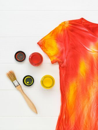 T-shirt in the style of tie dye, paint and brush on a white table. Staining fabric in tie dye style. Flat lay. 免版税图像