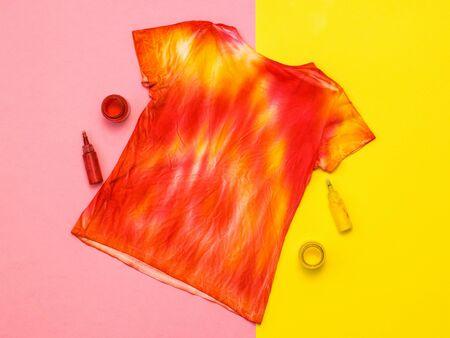 Camiseta estilo tie dye, pintura y pincel sobre un fondo amarillo y naranja. Tejido teñido en estilo tie dye. Endecha plana. Foto de archivo