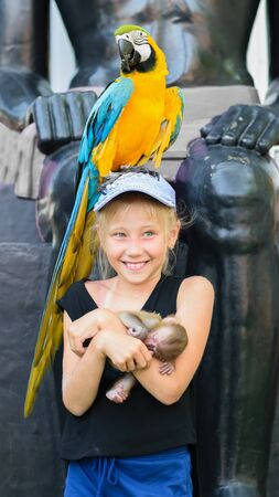 Girl with a parrot and a monkey on the background of a stone wall. Summer photo.