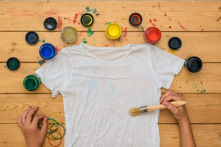 The girl begins to paint a white t-shirt in the style of tie dye. Staining fabric in tie dye style.