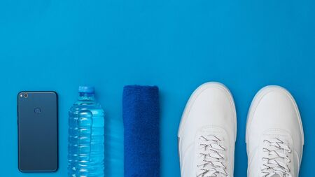 Smartphone, water bottle, towel and white sports shoes on blue background. Sports style. Flat lay. The view from the top. 写真素材