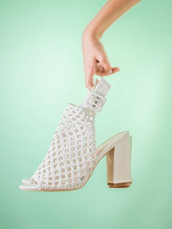 The hand of the child holds fashion summer shoes on a green background. Summer leather shoes for women.