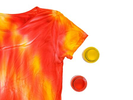 Yellow and red paint jars and tie Dye t-shirt isolated on white background. Staining fabric in tie dye style.