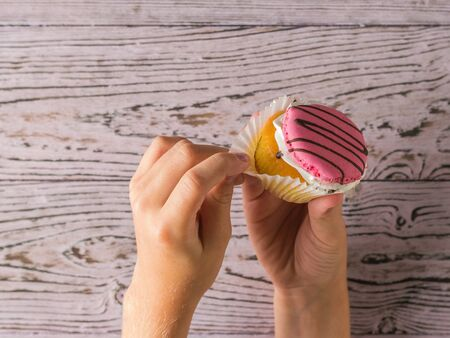 The girl takes the paper from a fresh cupcake. Freshly prepared homemade sweetness in the hands of a child.