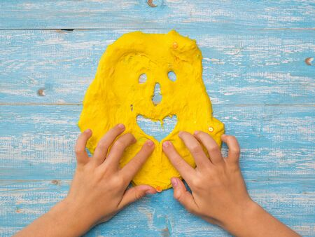The child makes a funny face of yellow slime on a blue table. Toy antistress. Toy for the development of hand motor skills.