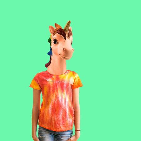 A girl with a unicorn head in a t-shirt in tie dye style on a green background. Modern art collage. Contemporary art.