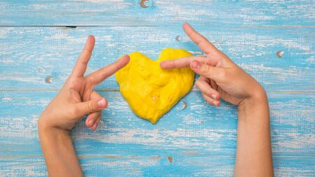 The child makes gestures with his fingers near the heart of the yellow slime on a wooden table. Toy antistress. Toy for the development of hand motor skills.
